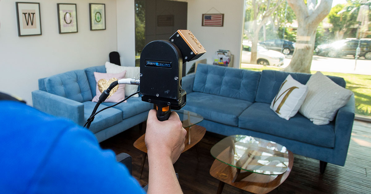 Image of 3D laser scanner capturing point cloud data in a residential living room during an As-Built survey site visit.